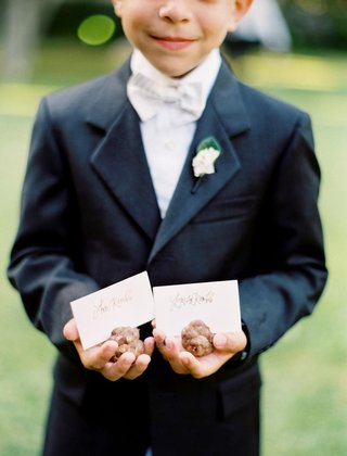 ring-bearer-in-a-dark-suit-and-bow-tie-holding-pinecone-place-card-holders