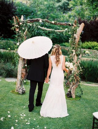 bride-in-a-monique-lhuillier-gown-with-groom-in-a-black-tuxedo-in-outdoor-wedding