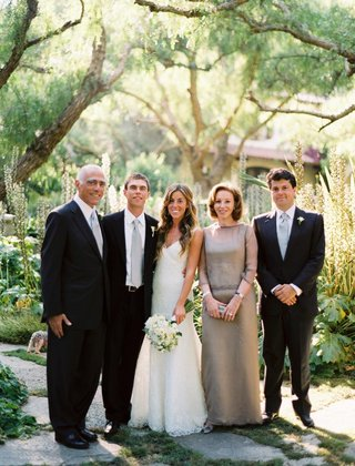 bride-in-a-monique-lhuillier-gown-with-groom-in-black-tuxedo-and-gray-tie-with-family