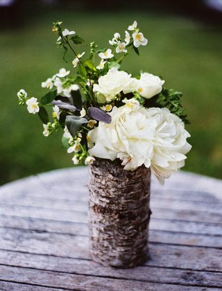outdoor-wedding-decor-of-vase-wrapped-in-birch-wood-filled-with-white-flowers-and-greenery