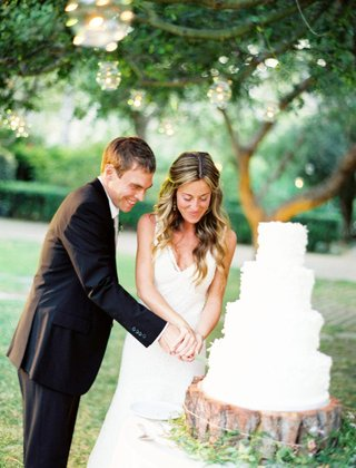 white-wedding-cake-being-cut-by-a-bride-in-a-monique-lhuillier-gown-and-groom-in-black-tuxedo