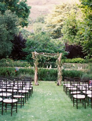 outdoor-wedding-ceremony-with-an-altar-made-of-driftwood-and-greenery