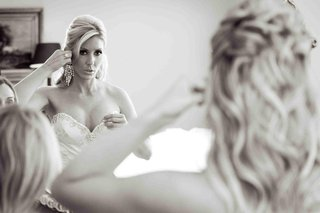 black-and-white-photo-of-a-bride-putting-on-chandelier-earrings