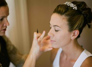 bride-with-updo-and-tiara-getting-makeup-done