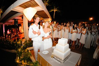 guests-watching-bride-and-groom-cut-white-cake
