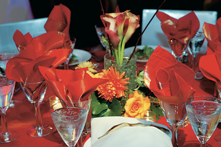 red-tablecloth-with-red-orange-and-yellow-flower-centerpiece