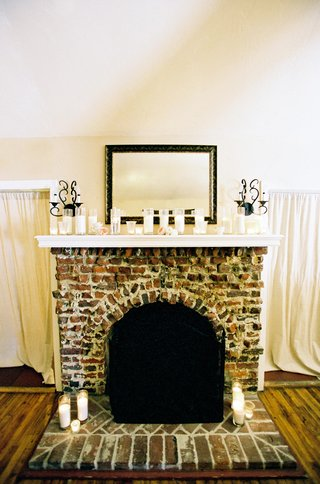 brick-fireplace-with-a-row-of-candles-on-mantle