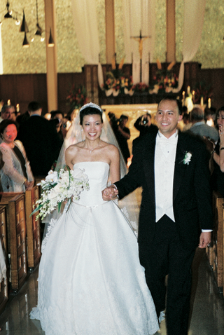 newlyweds-hold-hands-walking-up-aisle-of-church