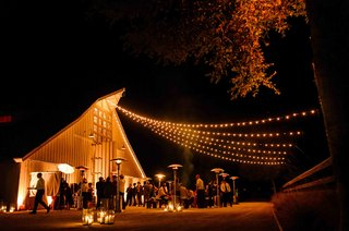 outdoor-cocktail-hour-with-string-lights-in-front-of-barn
