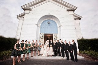 bridesmaids-and-groomsmen-with-couple-in-front-of-church