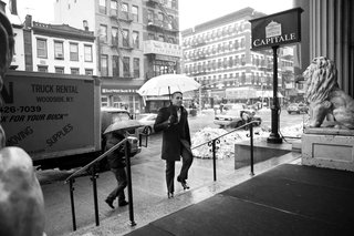 black-and-white-photo-of-groom-with-umbrella-at-capitale
