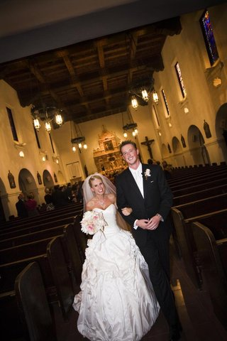 bride-and-groom-walk-up-aisle-in-catholic-church