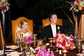 bride-and-groom-sit-at-head-of-reception-table