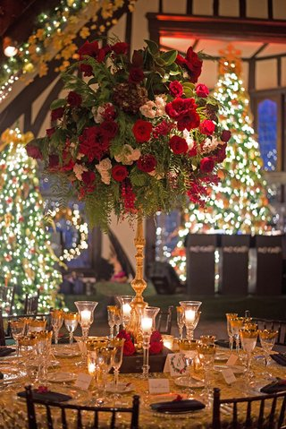 gold-wedding-reception-table-with-tall-red-green-and-white-flower-arrangement-and-christmas-trees