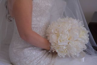 bride-in-embroidered-gown-holding-white-peony-flower-bouquet-with-ribbon-on-stems