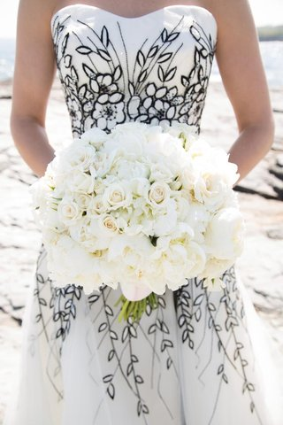 bride-in-black-and-white-dress-holds-all-white-bouquet