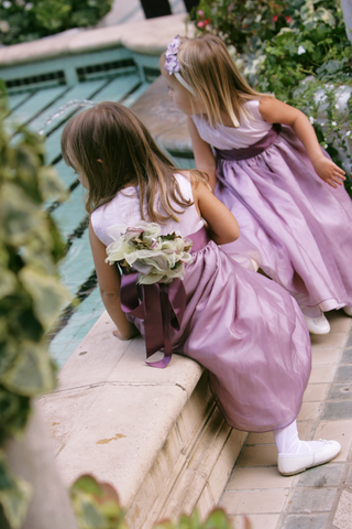 flower-girls-wearing-light-purple-dresses-with-dark-purple-sashes