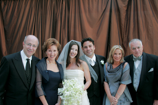 bride-and-groom-with-both-sets-of-parents-standing-in-front-of-brown-draping