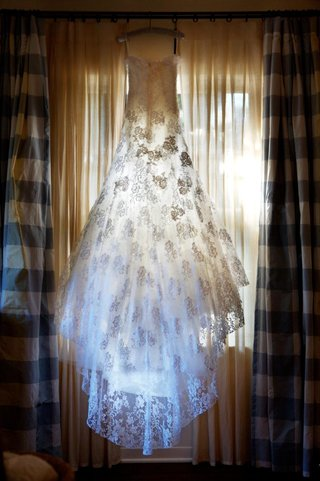 bridal-gown-hanging-in-bridal-suite-with-sun-shining-through