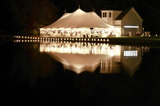 white-tent-wedding-on-lake-illuminated-with-lights
