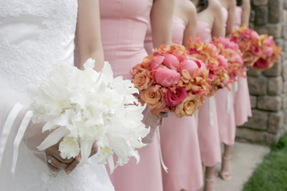 bride-with-a-bouquet-of-white-flowers-and-bridesmaids-with-bouquets-of-pink-and-orange-flowers