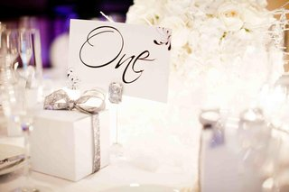 favor-box-wrapped-in-silver-ribbon-on-guest-table