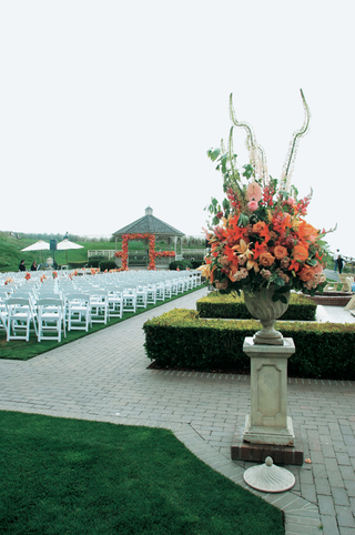 outdoor-wedding-ceremony-with-stone-urn-full-of-orange-and-pink-flowers