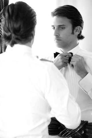 black-and-white-photo-of-groom-in-mirror-tying-bow-tie