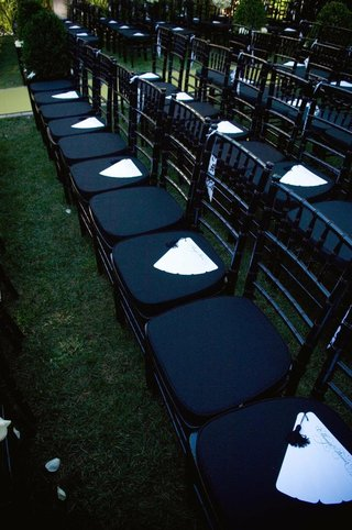 white-fan-style-wedding-program-on-ceremony-chairs