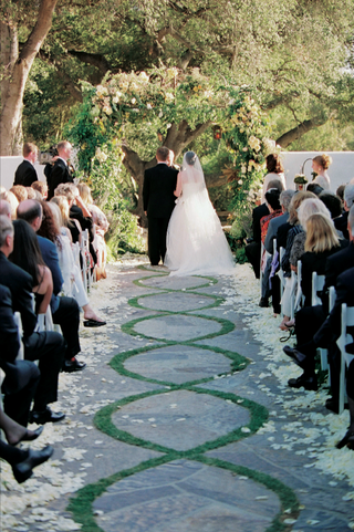 bride-and-groom-stand-at-end-of-stone-and-grass-patterned-aisle