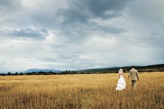bride-and-groom-walking-in-field-at-ranch-in-telluride-colorado