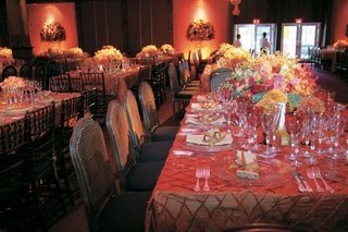 wedding-reception-tables-with-amber-tablecloths-and-colorful-centerpieces