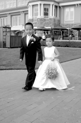 black-and-white-photo-of-flower-girl-carrying-a-pomander-bouquet-and-boy