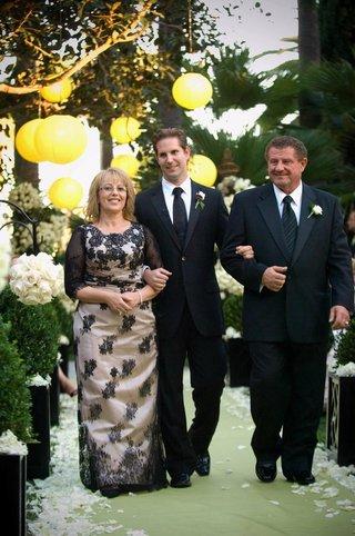 user-walks-mother-of-groom-down-garden-ceremony-aisle