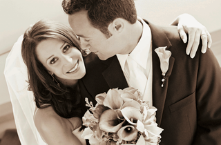 sepia-tone-image-of-bride-with-calla-lily-bouquet-and-groom