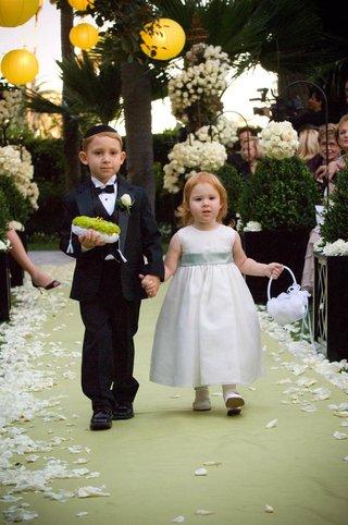 ring-bearer-and-flower-girl-walk-down-garden-ceremony-aisle