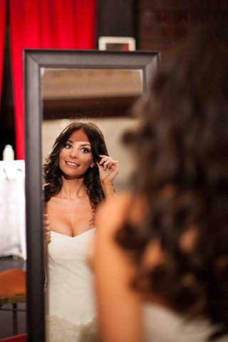 bride-looking-in-mirror-on-wedding-day-with-hair-down