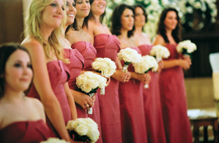 bridesmaids-at-ceremony-hold-white-rose-bouquets