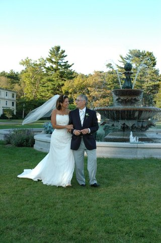 bride-and-groom-on-grass-lawn-in-front-of-fountain