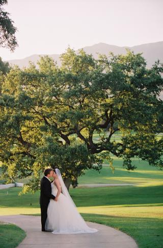 bride-and-groom-kiss-under-tree-at-ojai-valley-inn-spa
