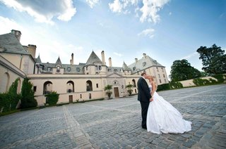 bride-in-a-strapless-pnina-tornai-ball-gown-kisses-groom-in-a-black-tuxedo-at-oheka-castle