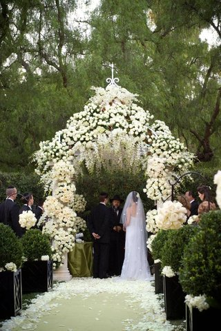 bride-and-groom-under-white-flower-ceremony-structure
