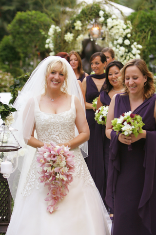 bride-in-an-a-line-gown-with-a-pink-orchid-bouquet-and-bridesmaids-in-purple-dresses