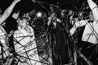 black-and-white-photo-of-bride-and-groom-leaving-wedding-metallic-streamers