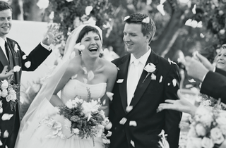 black-and-white-photo-of-couple-walking-up-aisle-with-petals