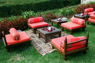 outdoor-seating-with-red-pillows-and-rugs