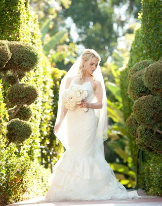 bridal-portrait-with-bouquet-in-front-of-green-hedges