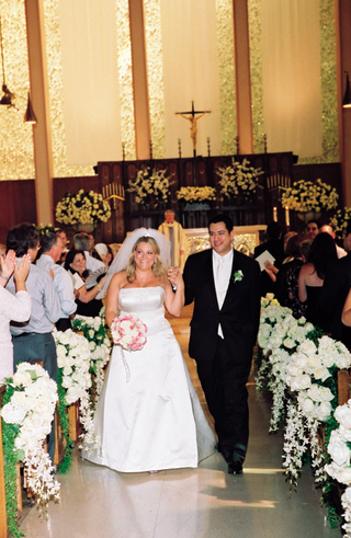 bride-and-groom-walk-up-ceremony-aisle-decorated-with-white-flowers
