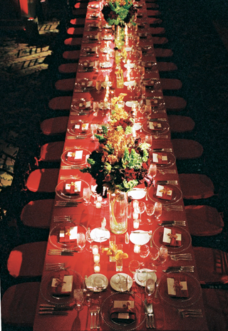 long-red-table-with-clear-chargers-candles-and-floewrs