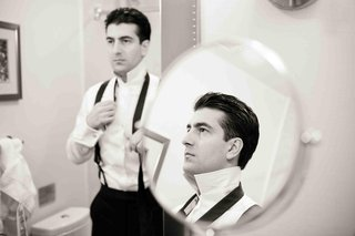 black-and-white-photo-of-groom-getting-ready-in-mirror